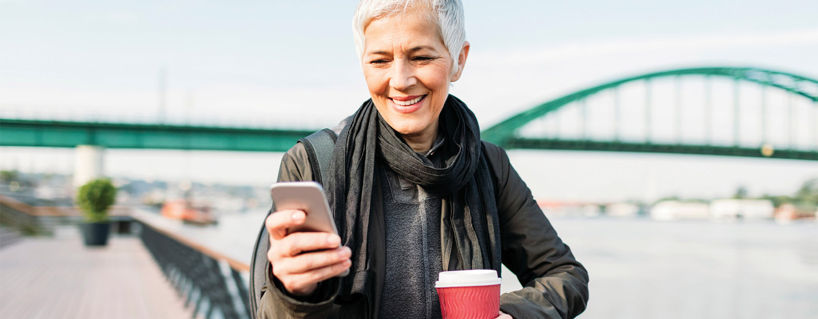 Image of woman site seeing while looking at her phone and holding a coffee.