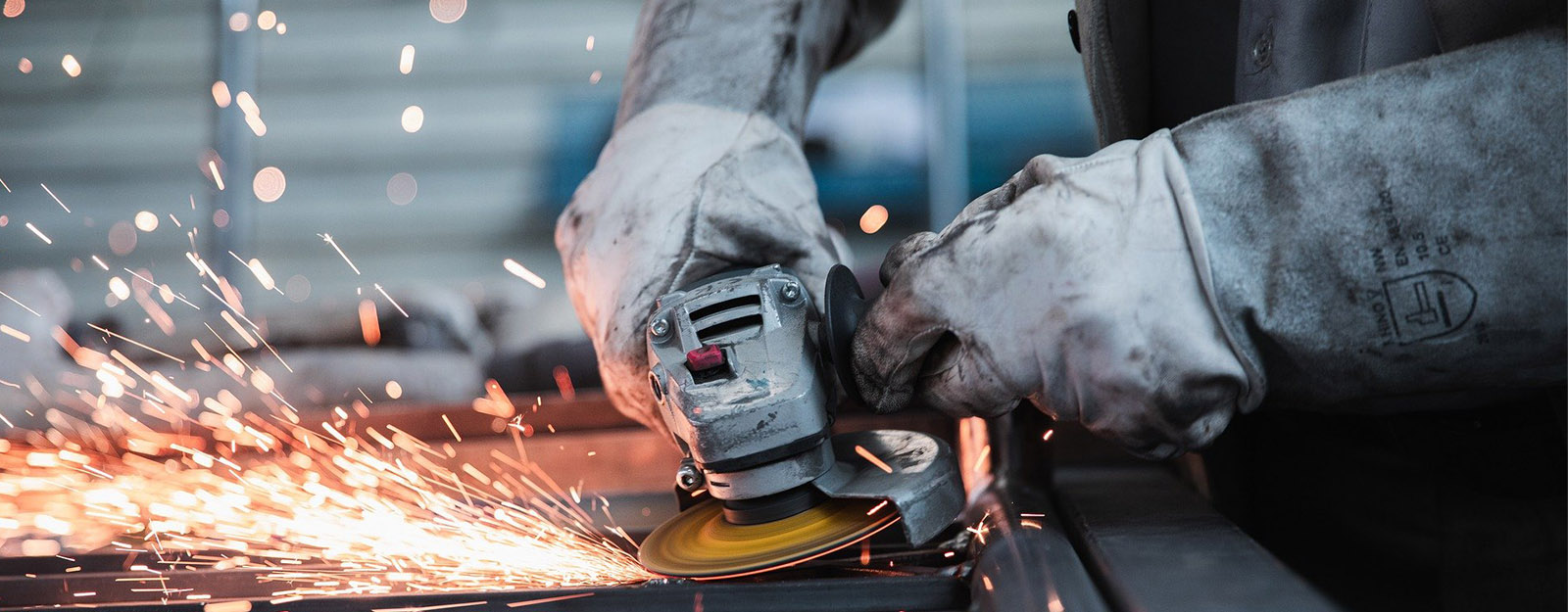 Worker wearing gloves using a hand grinder on metal with sparks flying.